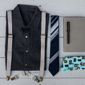 Grey leather suspenders with dark grey shirt,blue tie, socks, book and pen, flatlay