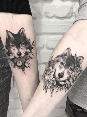 Two forearm black and white wolf tattoos each one surrounded by differing flower arrangements