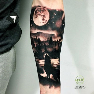 Black and white forearm tattoo of a wolf on the bank of a moon-light river howling towards the moon with fir trees and a hill