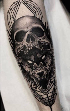 A forearm tattoo of a haunting growling wolf underneath a human skull with geometric designs in the background