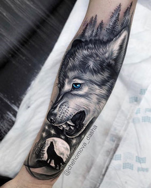 Black and white forearm tattoo of a young wolf with blue eyes looking down at a wolf silhouetted against a full moon and stars