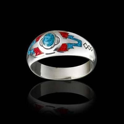 Wolvestuff's Sleeping Beauty Mountain Ring on a black background, made from sterling silver with a turquoise centre. ocean red coral arrow tips with intricate stamping along the band