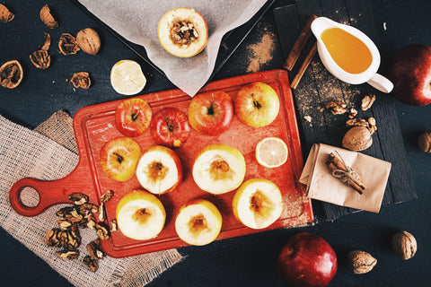 Picture of baked apples and ingredients on a black background
