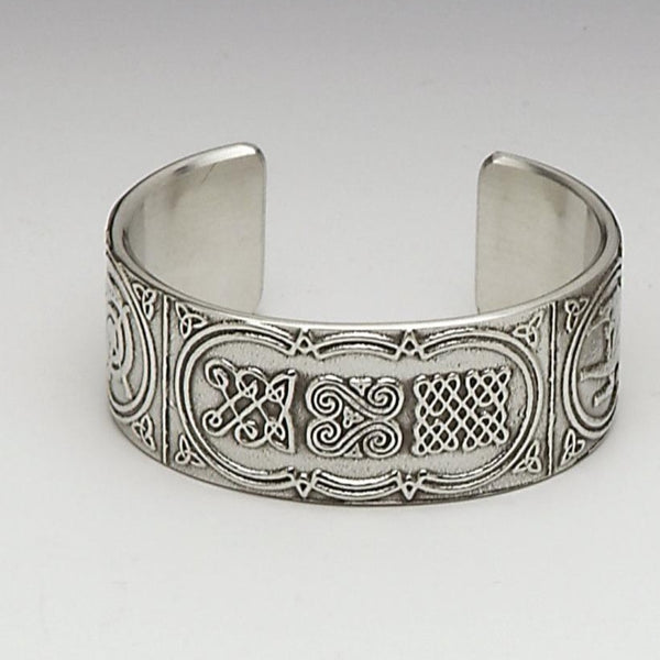 BANGLE BRACLET CELTIC. THIS MAKES A LOVELY GIFT FOR ANY WOMAN. THE CELTIC DESIGN IS TAKEN FROM THE BEALIN CROSS WHICH ONCE STOOD IN CLONMACNOISE. THE DESIGN IS THAT OF A HUNTING SCENE, CELTIC KNOT WORK AND ENTANGLED SWANS. THE BANGLE COMES BOXED IN A GREEN BANGLR BOX. PEWTER ZINN HARTZINN ÉTAIN PELTRO SILVER METAL