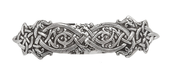 A HAIR BARRETTE WITH ENTWINED DRAGONS IN KELLS STYLE KNOTS.