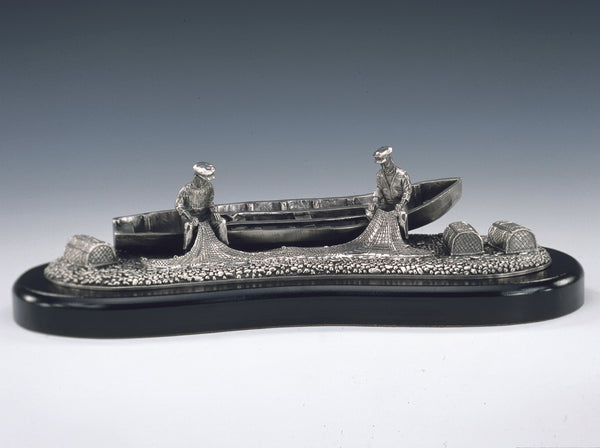 MEN OF ARAN PEWTER SCULPTURE OF FISHERMEN FROM ARAN MENDING THEIR NETS WHILE SITTING ON THE EDGE OF THEIR CURRAGH (BOAT) ALONG SIDE THEIR LOBSTER POTS. PEWTER SILVERWARE ZINN HARTZINN ÉTAIN PELTRO