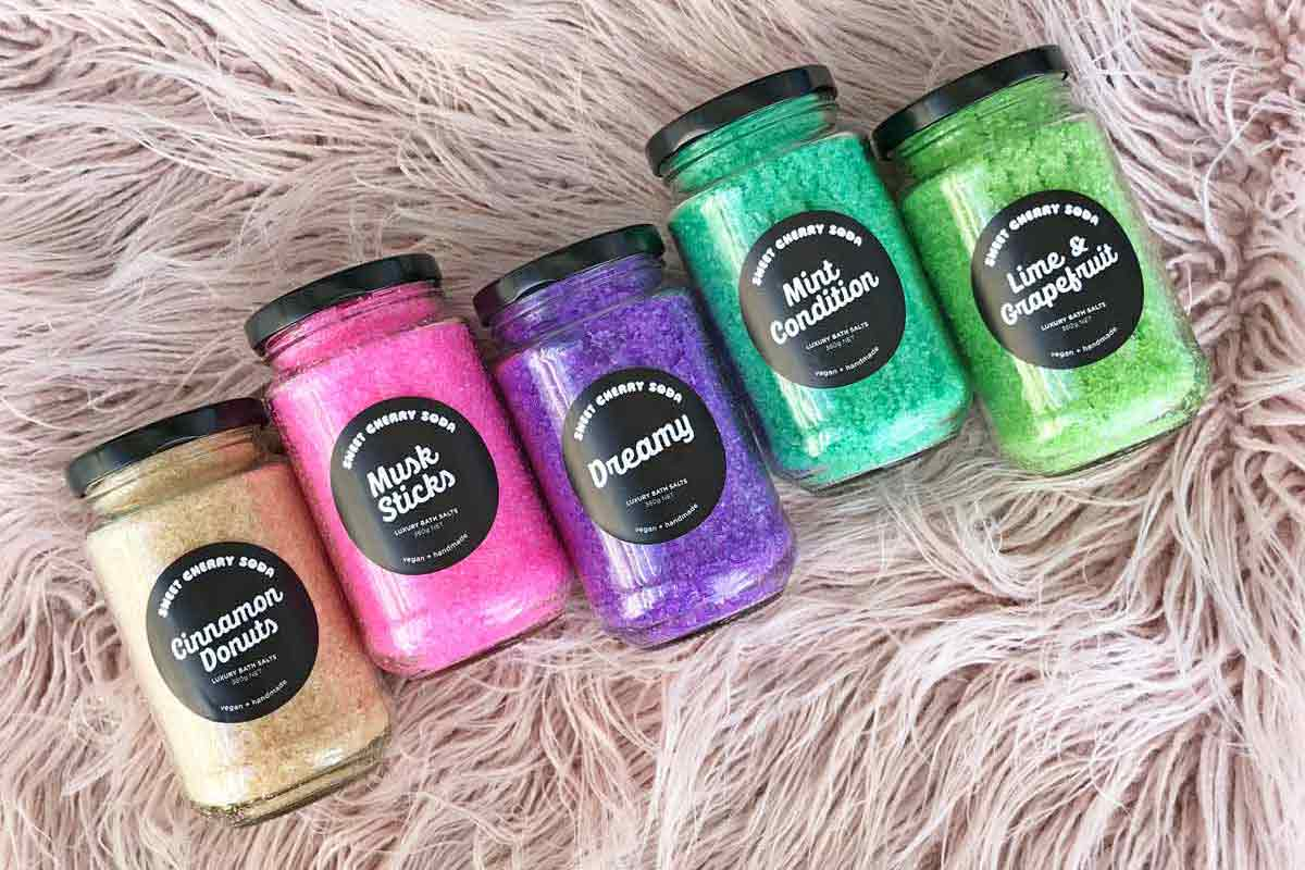 Jars of colourful bath salts against a pink furry background.