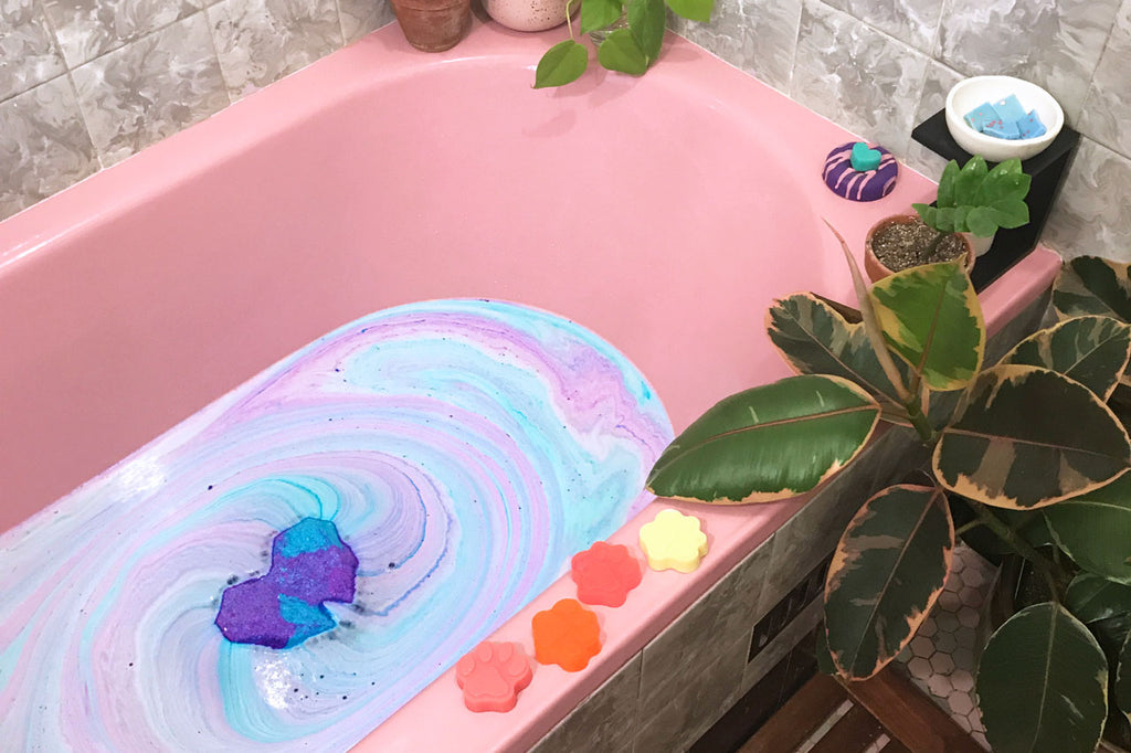 pink bathtub with plants and soap decorating the edge. a blue and purple bath bomb is swirling in the water.