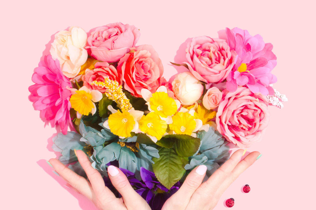 hands holding flowers arranged into a heart shape