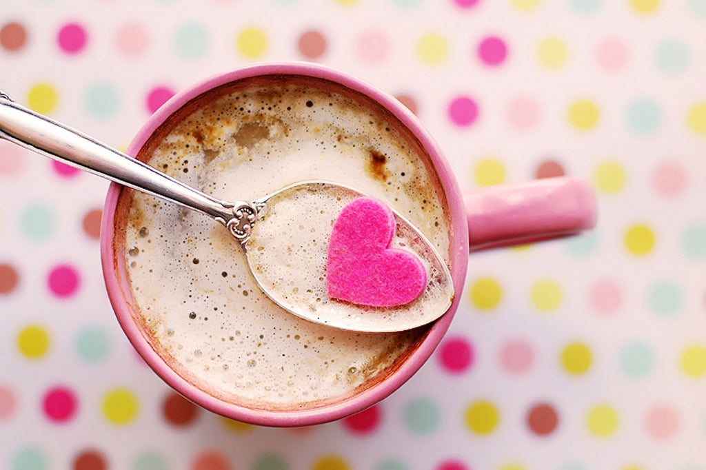 coffee in a pink cup on a spotted background. There's a spoon holding a heart shaped candy in it.