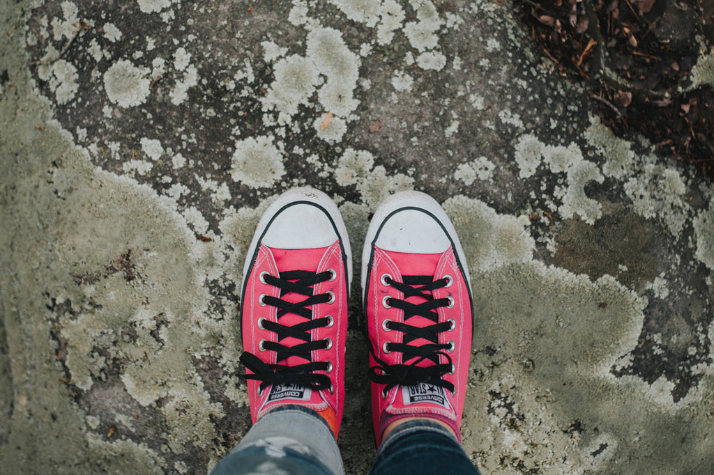 pink converse shoes with black shoelaces on a concrete floor.