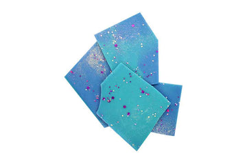 Blue and aqua soy wax melt shards with purple and silver bioglitter on top.