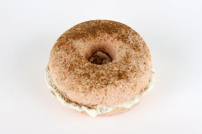 A 2-layered donut shaped bath bomb with solid bath bomb in the centre, sprinkled with cinnamon, on a white background.