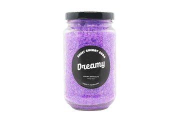 Jar of purple coloured bath salts with a black round label on the front.