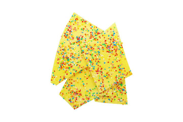 Yellow soy wax melt shards with colourful sprinkles on top.
