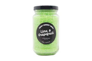 Jar of green coloured bath salts with a black round label on the front.