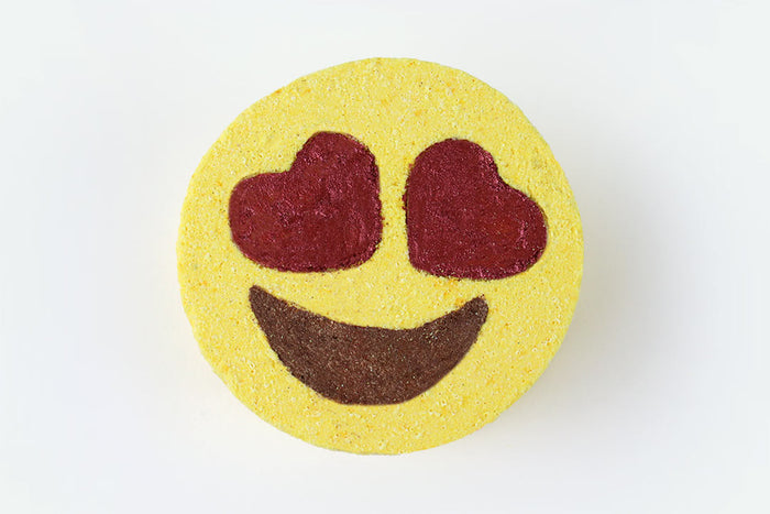 A bath bomb in the shape of the heart-eyes emoji - a yellow disk with red heart shaped eyes and a brown smiley mouth, on a white background.