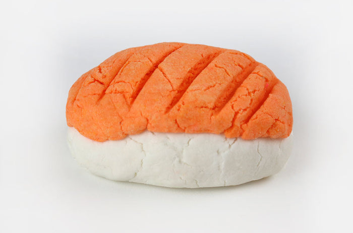 Solid bubble bath in the shape of a sake nigiri sushi piece, white on the bottom and salmon orange on top, on a white background.