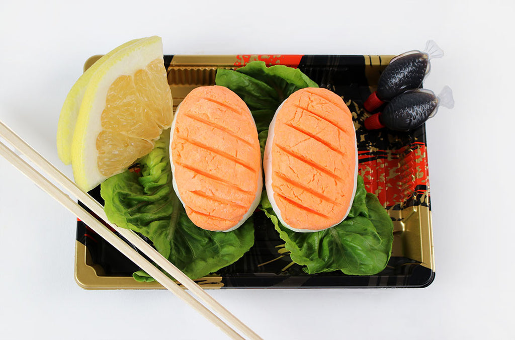A mock-up of a sushi box - 2 pieces of sake nigiri bubble bath in a sushi box upon lettuce, with chopsticks and soy sauce, on a white background.