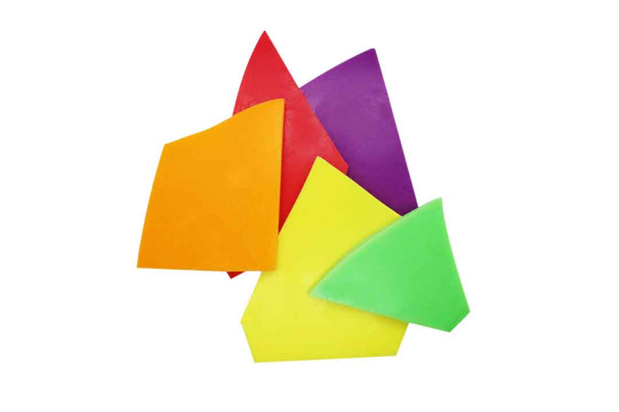 Soy wax melt shards in yellow, orange, green, purple, and red.