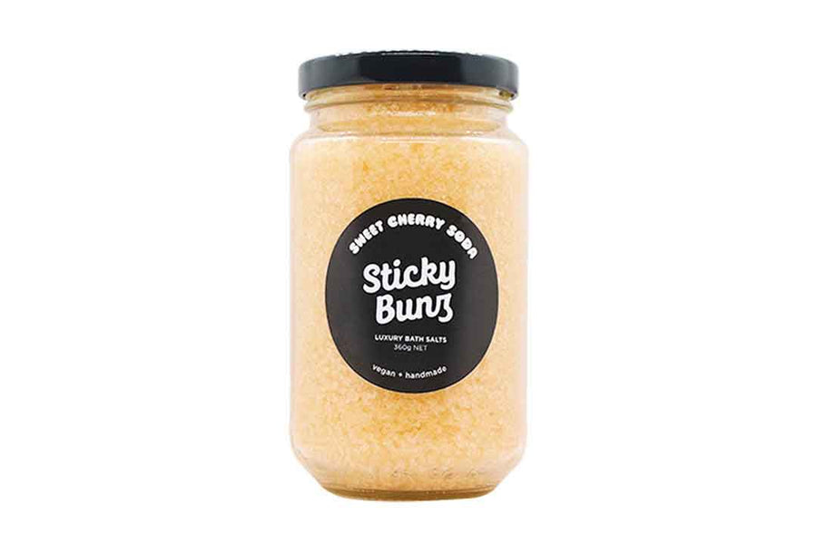 Jar of orange coloured bath salts with a black round label on the front.