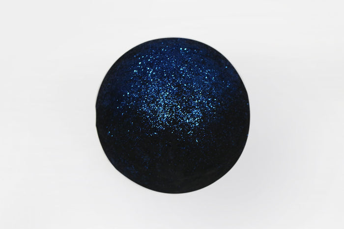 A spherical black bath bomb with dark blue glitter sprinkled on top, on a white background.