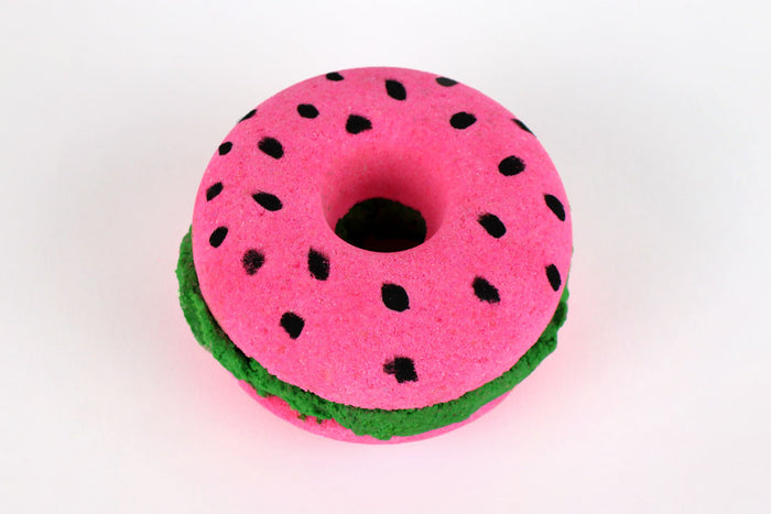 A 2-layered pink donut shaped bath bomb with green solid bath bomb in the centre, with black dots on top made to look like watermelon seeds, on a white background.
