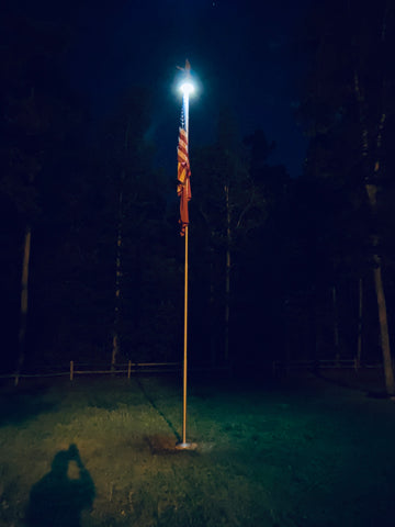 Flagpole at night with topper disc light