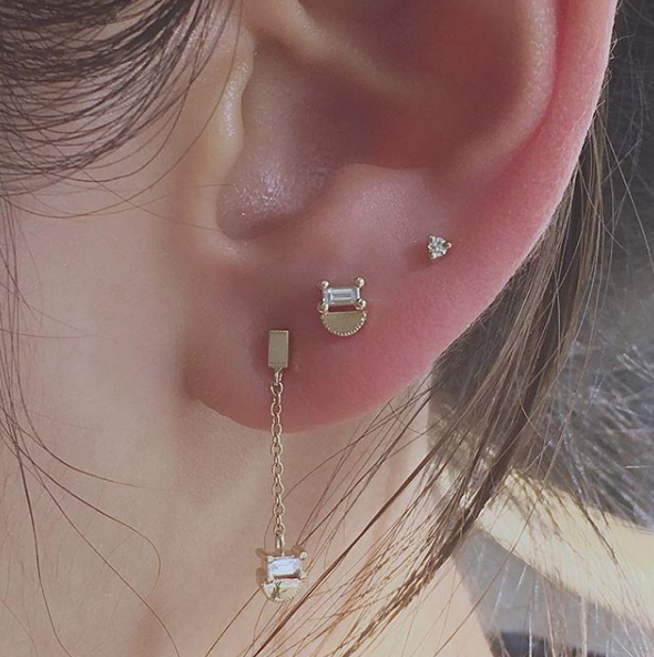 JKD baguette half moon stud stacked with other pieces on ear