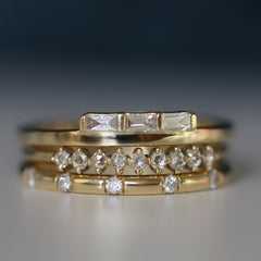 detail, JKD stack of baguette style and diamond detail rings in yellow gold