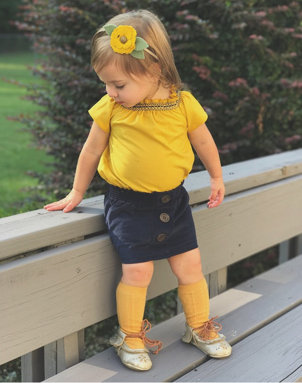 Toddler Girl Fall outfit of mustard smock top and navy corduroy skirt by duchess and goose