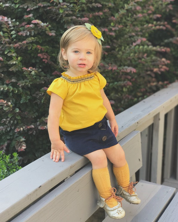 Toddler Girl wearing mustard smock top and navy corduroy smock skirt by duchess and goose