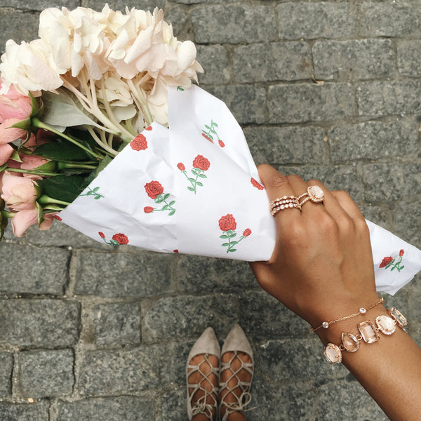 woman wearing rose gold bracelet and ring holding flowers