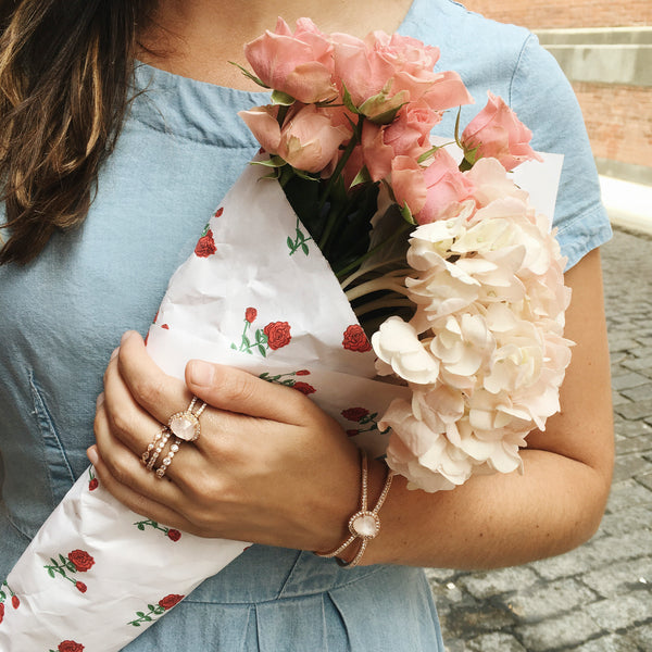 woman wearing rose gold bracelets and rings holding flowers