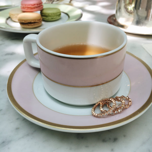 chloe + isabel Petits Bijoux Stackable rose gold rings against a pink, cream, and gold tea cup