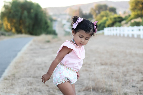 Toddler wearing pink smock top unicorn bubble shorts by Duchess and Goose