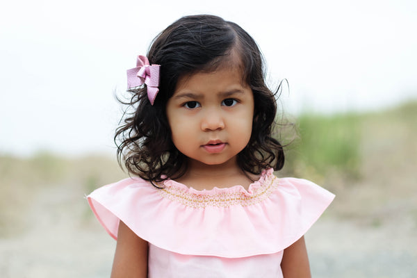 Toddler wearing pink smock top with gold smocking by Duchess and Goose