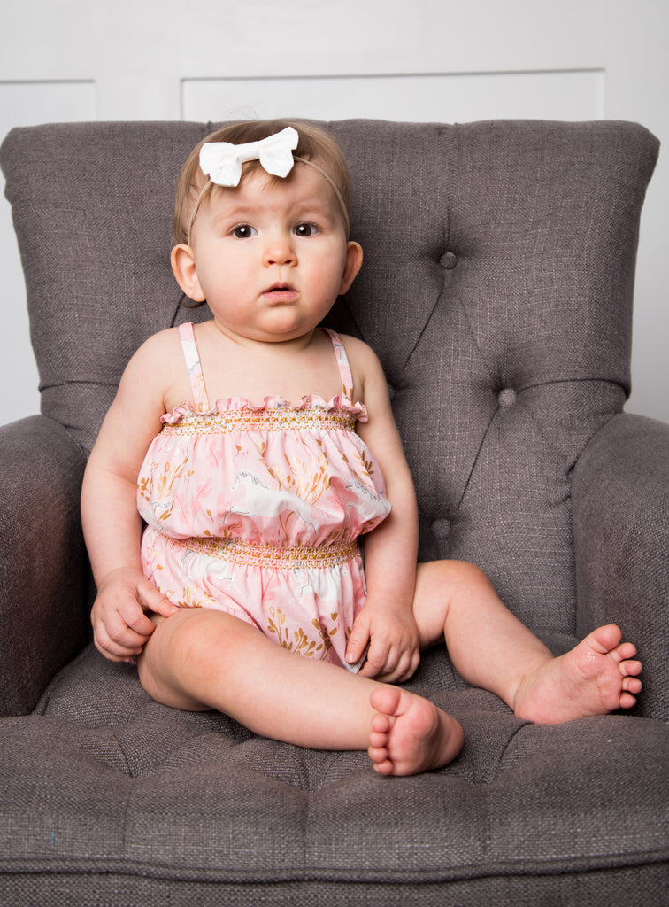 baby girl wearing pink handmade smocked bubble romper by Duchess and Goose
