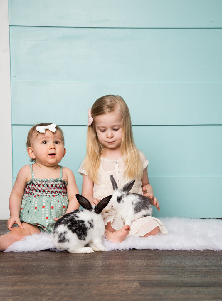 baby wearing handmade smock romper by duchess and goose with bunnies for easter photo shoot