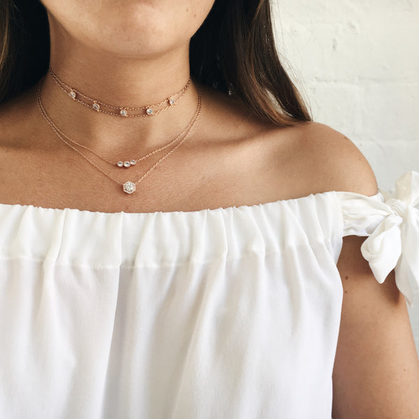 rose gold necklaces layered against off shoulder white shirt