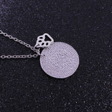 Silver necklace chain with paw print charm with circular pendant.