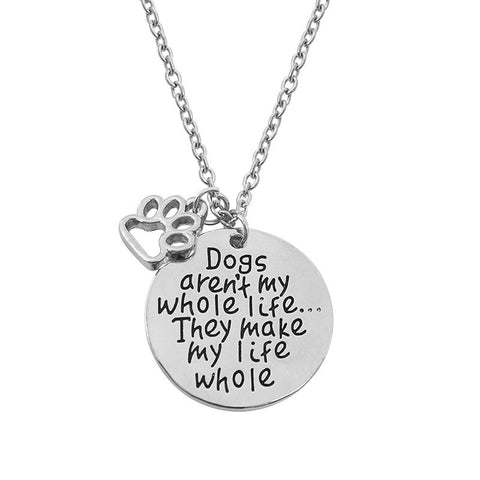 "Silver necklace chain with paw print charm with circular pendant that says, ""Dogs aren't my whole life...They make my life whole"