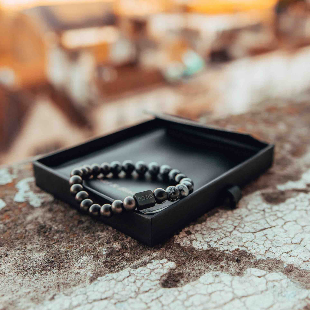 Snowflake Obsidian Bead Bracelet - Our Snowflake Obsidian Bead Bracelet Features 8mm Natural Stones, Premium Elastic Cord and Brushed Black Hardware. A Beautiful Addition to any Collection.