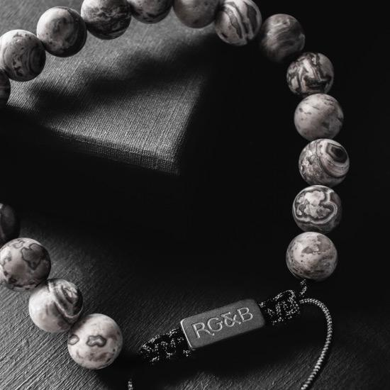 Grey Jasper Bead Bracelet - Our Grey Jasper Bead Bracelet Features Natural Stones, Waxed Cord and Brushed Black Steel Hardware. A Beautiful Addition to any Collection.