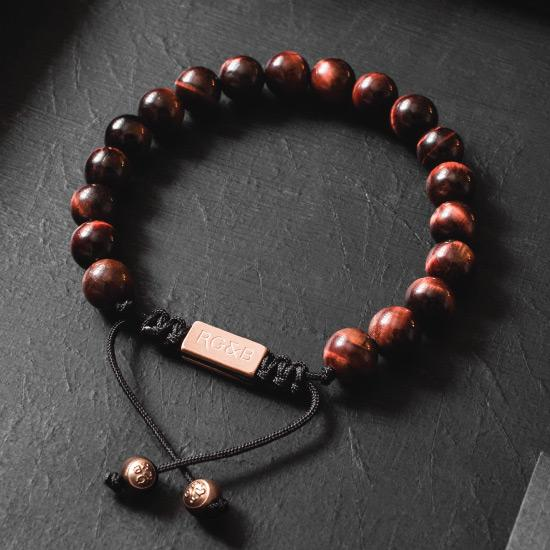 Red Tiger Eye Bead Bracelet - Our Red Tiger Eye Bead Bracelet Features Natural Stones, Waxed Cord and Brushed Rose Gold Steel Hardware. A Beautiful Addition to any Collection.