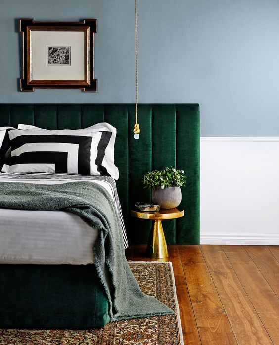 Dark green bedhead in classic bedroom with gold accents.