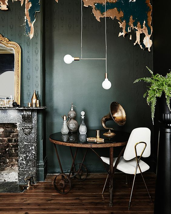 Dark green interior with greenery and dark wood accents.