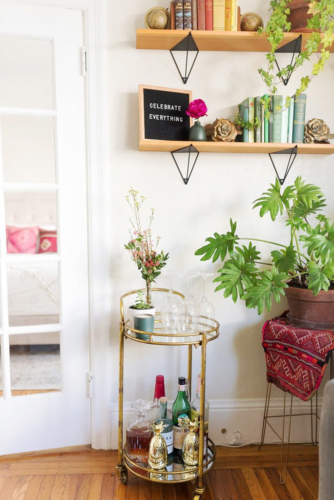 Brass bar cart with wooden shelves and plant stands