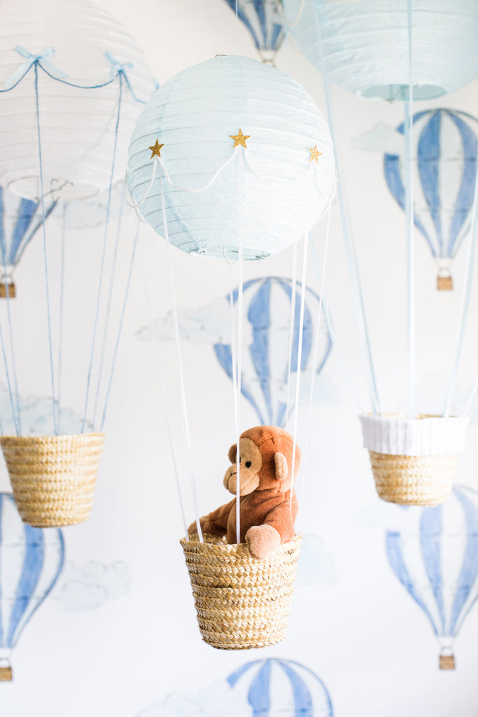 Boy's room interior decor with hot air balloons and blue wallpaper.