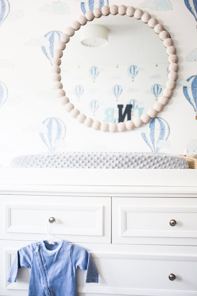 Boy's nursery interior in white, blue and grey with wooden accents.